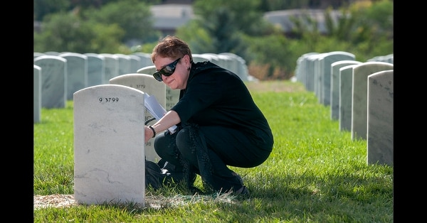 Patricia Duran visits the grave of her uncle, WWII Army Air Forces Sgt. Alfonso Duran, following his burial service at the Santa Fe National Cemetery in Santa Fe on Aug. 22, 2018. (Eddie Moore/The Albuquerque Journal via AP)