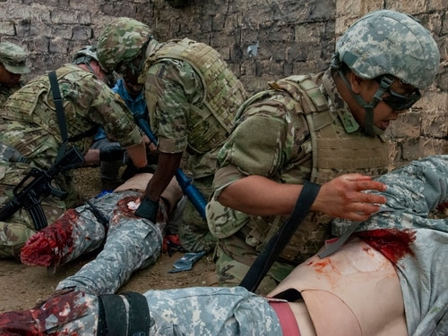 Spc. Cher Lee (right), a U.S. Army Reserve Soldier with the 13th Psychological Operations Battalion, from Arden Hills, Minnesota, calls out a nine-line medevac while evaluating a dummy during a medical training exercise at Fort McCoy, Wisconsin, July 18, 2019. (Sgt. Alicia Pennisi/Army)
