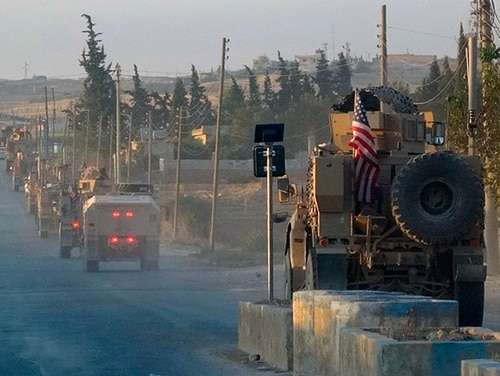 In this image provided by Hawar News Agency, ANHA, U.S. military vehicles travel down a main road in northeast Syria, Monday, Oct. 7, 2019. U.S.-backed Kurdish-led forces in Syria said American troops began withdrawing Monday from their positions along Turkey's border in northeastern Syria, ahead of an anticipated Turkish invasion that the Kurds say will overturn five years of achievements in the battle against the Islamic State group. (ANHA via AP)