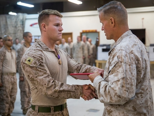 UNDISCLOSED LOCATION, SOUTHWEST ASIA – Cpl. Nathan Rousseau (left), a mortar Marine with 3rd Battalion, 4th Marine Regiment attached to Special Purpose Marine Air-Ground Task Force, Crisis Response-Central Command, receives the Purple Heart from Lt. Gen. Carl Mundy (right), the commander of Marine Corps Forces Central Command, during a Purple Heart Ceremony, Oct. 21. Rousseau received the Purple Heart for wounds sustained in Syria while deployed in support of operations for SPMAGTF-CR-CC. (Cpl. Gabino Perez/Marine Corps)
