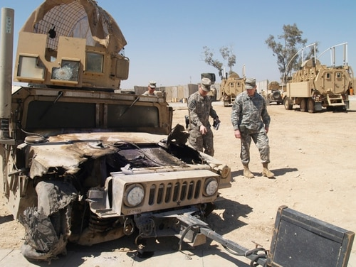 Then-U.S. Army Europe commander Gen. Carter F. Ham, at the U.S. Army Patrol Base in Al Hillah, looks over damage caused to a Humvee the day before during a patrol in the area in 2009. The Humvee was hit by an EFP, (explosively formed projectile), a roadside bomb of the type believed to be supplied by Iran. (David Rising/AP)