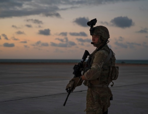 U.S. Army Spc. Ryan Roman provides perimeter security for a C-130J Super Hercules as it unloads cargo in Somalia on Dec. 31, 2019. (Tech. Sgt. Nick Kibbey/Air Force)