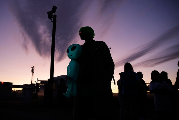 Chase Hansen holds an inflatable alien near an entrance to the Nevada Test and Training Range near Area 51, Friday, Sept. 20, 2019, near Rachel, Nev. People came to visit the gate inspired by the