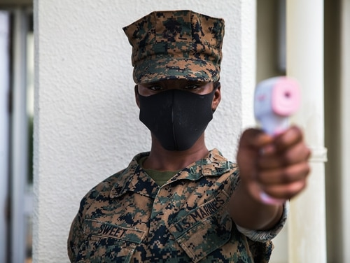 U.S. Marine Corps Lance Cpl. Denya Sweet conducts temperature checks in front of the dining facility on Camp Courtney, Okinawa, Japan, July 13, 2020. (Lance Cpl. Juan Carpanzano/Marine Corps)