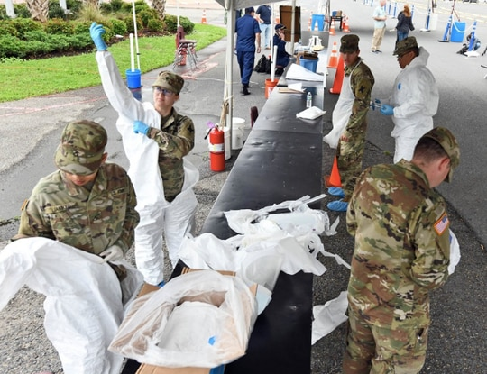 Louisiana National Guardsmen with the 256th Infantry Brigade Combat Team don protective suits to administer nasal swabs to first responders and medical personnel that exhibit COVID-19 symptoms at a mobile testing site at the Alario Center in Westwego, Louisiana, March 21, 2020. (U.S. Army National Guard photo by Staff Sgt. Garrett L. Dipuma)