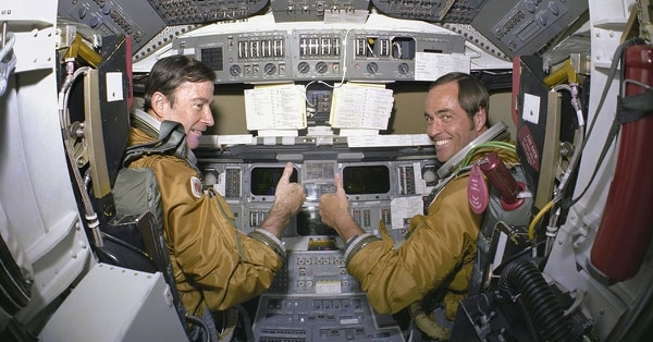 In this 1980 photo made available by NASA, astronauts for the first space shuttle mission, Commander John Young and Pilot Robert Crippen, take a break from their intensive training schedule to pose for pictures on the flight deck of the space shuttle Columbia at the Kennedy Space Center in Florida. NASA says Young, who walked on the moon and later commanded the first space shuttle flight, died on Friday, Jan. 5, 2018. He was 87. (NASA via AP)