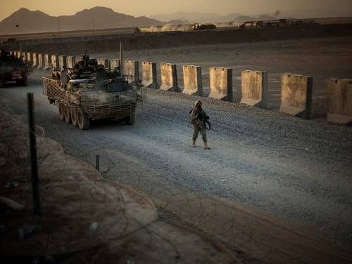 U.S. soldiers walk next to armored vehicles as they arrive at their base on the outskirts of Spin Boldak, about 100 kilometers (63 miles) southeast of Kandahar, Afghanistan, on June 13. (Emilio Morenatti/AP)