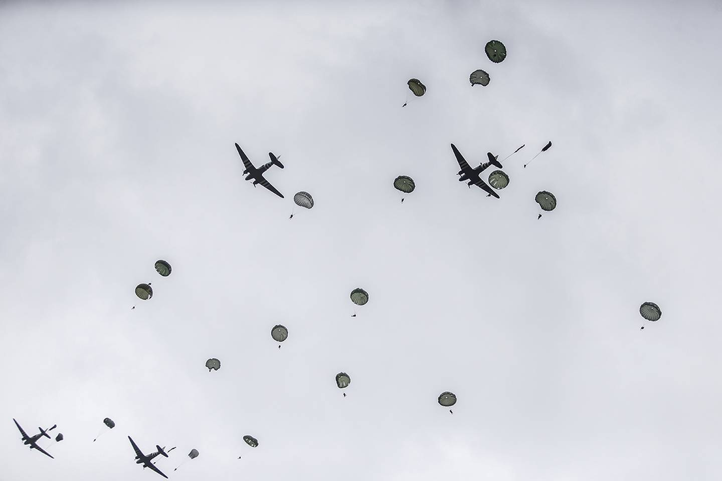 Parachutists jump from C-47 transport planes in Carentan, Normandy, France.