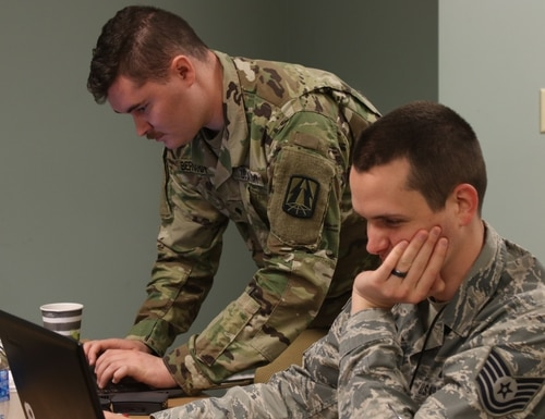U.S. Army Spc. Cody Bernardy, assigned to the Army Reserve Cyber Operations Group (ARCOG), North Central Cyber Protection Center, 335th Signal Command (Theater), analyzes network data with an Air Force Tech Sgt. during Cyber X-Games 2019. (U.S. Army Reserve photo by Sgt. Erick Yates)