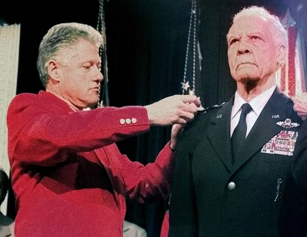 """FILE--In this Dec. 9, 1998 file photo, President Clinton pins a fourth star on the shoulder of Lt. Gen. Benjamin O. Davis Jr., USAF retired, during a ceremony honoring his service in Washington. Davis Jr. entered West Point in 1932 as its only black cadet and spent the next four years shunned. He roomed alone and ate alone. The future Tuskegee Airman and trailblazing Air Force general later recalled he was """"an invisible man."""" Now more than a decade after his death, the academy that ostracized Davis is honoring him. (AP Photo/Greg Gibson, File)"""