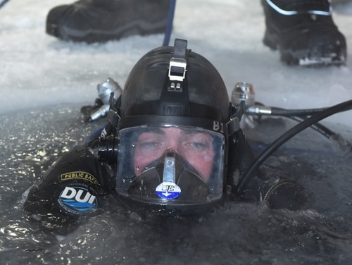 Coast Guard Diver 1st Class Dylan Smith, assigned to Regional Dive Locker West, dives into a water hole during a torpedo exercise in the Arctic Circle in support of Ice Exercise 2018. (Mass Communication Specialist 1st Class Daniel Hinton/Navy)