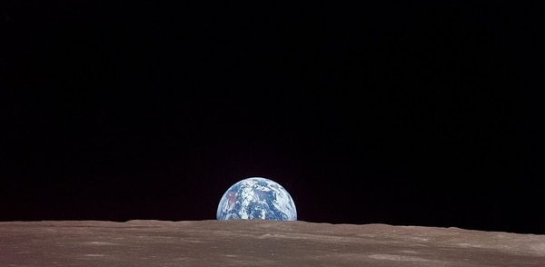 This view from the Apollo 11 spacecraft shows the Earth rising above the Moon's horizon. The lunar terrain pictured is in the area of Smyth's Sea on the nearside. Coordinates of the center of the terrain are 86 degrees east longitude and 3 degrees north latitude. While astronauts Neil A. Armstrong, commander, and Edwin E. Adrin, Jr., lunar module pilot, descended in the Lunar Module (LM)