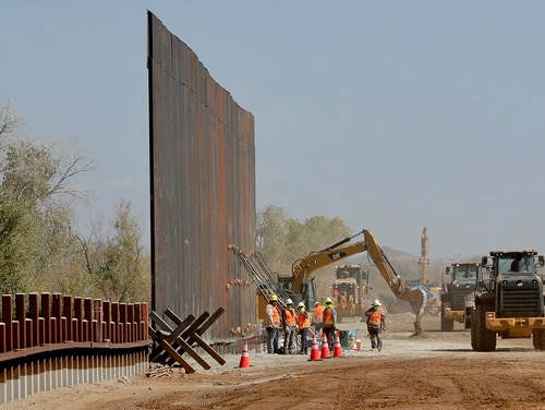 Government contractors erect a section of Pentagon-funded border wall along the Colorado River on Sept. 10, 2019, in Yuma, Ariz. (Matt York/AP)