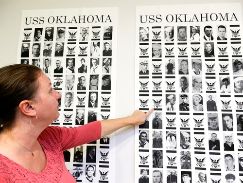 In this Sept. 18, 2018, photo, Dr. Carrie Brown, forensic anthropologist and director of the USS Oklahoma Project at the Defense POW/MIA Accounting Agency (DPAA) Identification laboratory, points to images on posters showing the names and photos of the victims of the USS Oklahoma, sunk by the Japanese in Pearl Harbor. (Nati Harnik/AP)