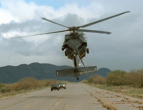 A CBP Air unit UH-60 Blackhawk helicopter intimidates two vehicles on a remote air strip in America's southwest border region.