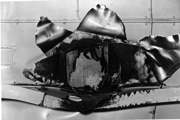 View of the underside of the aircraft carrier Yorktown's flight deck structure, showing the impact hole made by the Japanese bomb that struck amidships during the Battle of Coral Sea on May 8, 1942. This bomb penetrated several decks before exploding, killing or seriously injuring 66 crewmen. This view looks upward, with a patch over the flight deck visible within the hole. Note structural beam in lower part of the photo, distorted by the bomb's passage. (U.S. Naval History and Heritage Command)