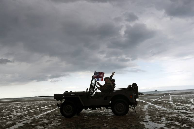Enthusiasts ride a jeep on the beach of Arromanches