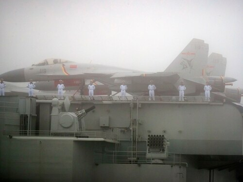 Sailors stand near fighter jets on the deck of the Chinese People's Liberation Army (PLA) Navy aircraft carrier Liaoning as it participates in a naval parade to commemorate the 70th anniversary of the founding of China's PLA Navy in the sea near Qingdao on April 23, 2019. (Mark Schiefelbein/AFP via Getty Images)