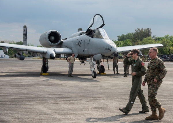 An Air Force pilot, left, and Marine Corps Brig. Gen. Christopher McPhillips walk past A-10 Thunderbolt IIs preparing totake off at Clark Air Base, Philippines, April 5 during Exercise Balikatan. (Senior Airman Sadie Colbert/Air Force)