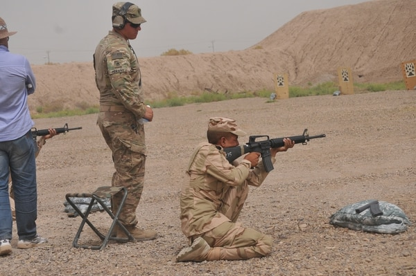 U.S. Army Staff Sgt. William Meravy, left, a trainer with Company A, 1st Battalion 502nd Infantry Regiment, Task Force Strike, watches as an Iraqi army ranger student engages targets in the kneeling position at Camp Taji, Iraq July 3, 2016,. To pass the qualification event, the students had to score based on U.S. Army marksmanship standards. Camp Taji is one of four Combined Joint Task Force – Operation Inherent Resolve building partner capacity locations dedicated to training Iraqi security forces. (U.S. Army photo by 1st Lt. Daniel Johnson/Released)