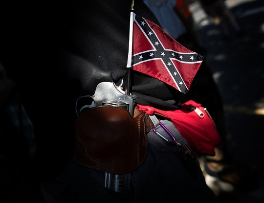 A man carrying a sidearm and Confederate flag attends a protest held by the Tennessee based group