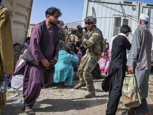 An 82nd Airborne soldier shouts and raises his weapon towards an Afghan passenger at the Kabul airport in Kabul on August 16, 2021, after a stunningly swift end to Afghanistan's 20-year war, as thousands of people mobbed the city's airport trying to flee the group's feared hardline brand of Islamist rule. (Photo by WAKIL KOHSAR/AFP via Getty Images)
