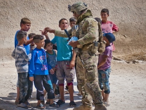 A U.S. soldier hands out candy to a group of kids during a patrol in their village along the demarcation line outside Manbij, Syria, July 14, 2018. (Staff Sgt. Timothy R. Koster/Army)