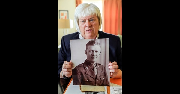 In this Sept 27, 2018, photo, Joani McGinnis of Shenandoah, Iowa, holds a photo of her uncle, Sgt. Melvin C. Anderson, who died in 1944 in the battle of the Hurtgen Forest in Germany, and was recently identified by the Defense POW/MIA Accounting Agency (DPAA) Identification laboratory at Offutt AFB in Bellevue, Neb. Sgt. Anderson will be buried at the Omaha National Cemetery on Oct. 12, 2018. (Nati Harnik/AP)