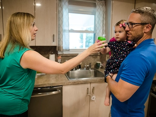 In this Aug. 1, 2018, photo, Lauren Woehr hands her 16-month-old daughter Caroline, held by her husband Dan McDowell, a cup filled with bottled water at their home in Horsham, Pa. In Horsham and surrounding towns in eastern Pennsylvania, and at other sites around the United States, the foams once used routinely in firefighting training at military bases contained per-and polyfluoroalkyl substances, or PFAS. EPA testing between 2013 and 2015 found significant amounts of PFAS in public water supplies in 33 U.S. states. (Matt Rourke/AP)