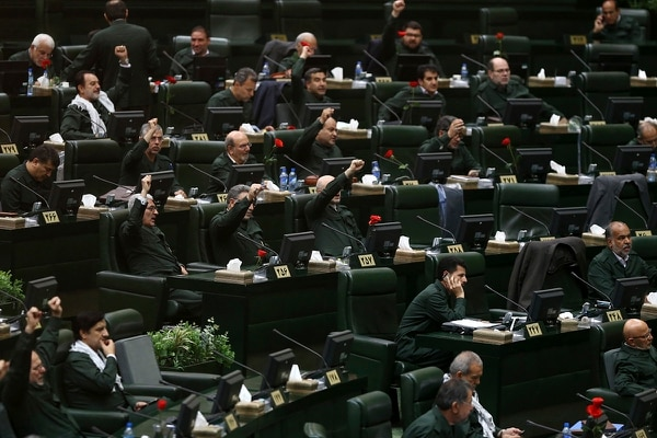 Wearing the uniform of the Iranian Revolutionary Guard, lawmakers chant slogan during an open session of parliament in Tehran, Iran, Tuesday, April 9, 2019. (Hamidreza Rahel/ICANA via AP)