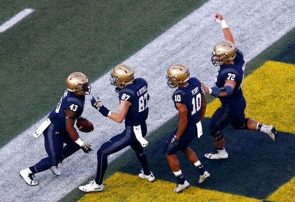 Navy fullback Nelson Smith, left, celebrates his touchdown with teammates Ryan Mitchell, Malcolm Perry and Ford Higgins in the first half of an NCAA college football gameagainst Tulsa on Saturday in Annapolis. (Patrick Semansky/AP)