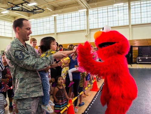 Sesame Street's Elmo gives a high-five to an audience member after a Sesame Street USO Experience for Military Families show at Travis Air Force Base, Calif., in June, 2016. (Louis Briscese/Air Force)