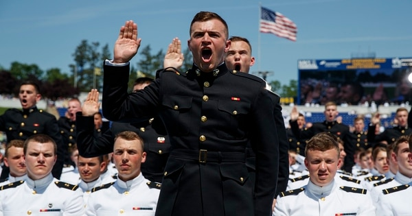 Midshipmen are sworn in during a graduation and commissioning ceremony at the Naval Academy on Friday in Annapolis, Md. (Evan Vucci/AP)