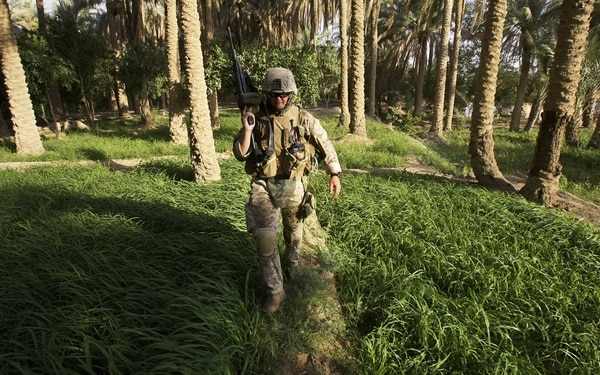U.S. Marine Lance Cpl. Bradley Hewitt, of Canal Winchester, Ohio, from Lima Company of the 3rd Battalion, 25th Regimen from Ohio, walks through a palm grove in Parwana, near Haditha, Iraq, Friday, Aug. 5, 2005. On Wednesday, a roadside bomb nearby killed 14 Marines and a civilian interpreter, in the deadliest roadside bombing suffered by American forces in the Iraq war. (AP Photo/Jacob Silberberg)