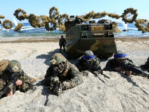 U.S. Marines, left, and South Korean Marines, wearing blue headbands on their helmets, take positions after landing on the beach during a joint military combined amphibious exercise in Pohang, South Korea. (Kim Jun-bum/Yonhap via AP)