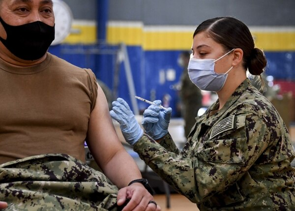 Hospital Corpsman 2nd Class Angelina Mangram, assigned to Fleet Surgical Team 3, administers the COVID-19 vaccine at the Naval Base San Diego fitness center on Jan. 6, 2021. (Mass Communication Specialist 1st Class Julio Rivera/Navy)
