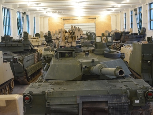 Abrams tanks and Bradley vehicles are stored in a warehouse in Mumaiciai, Lithuania, as part of a U.S. Army storage site for equipment. (Maj. Randy Ready/U.S. Army)