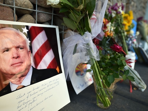 Photographs, flowers and notes gather at a makeshift memorial to Sen. John McCain outside his office in Phoenix on Aug. 26, 2018. (Robyn Beck/AFP via Getty Images)