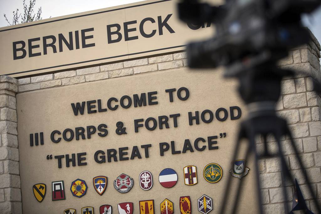 In this April 2, 2014, file photo, members of the media wait outside of the Bernie Beck Gate, an entrance to the Fort Hood military base in Fort Hood, Texas
