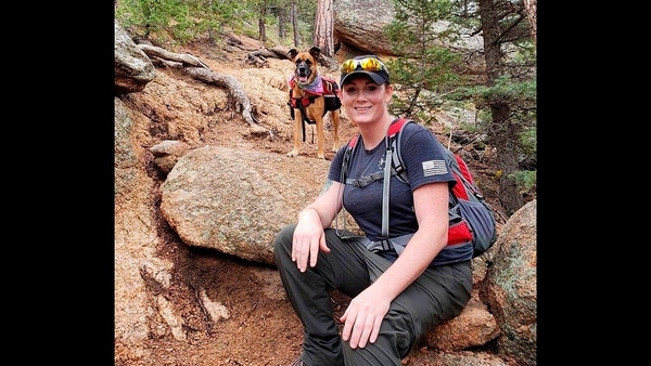 This undated photo provided by her wife Jessica Kibodeaux shows Lindsey Muller and her dog Emma hiking in the Cheyenne Mountains west of Fort Carson, Colo. (Jessica Kibodeaux via AP)