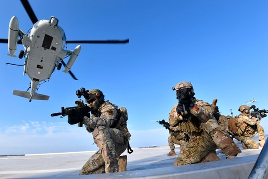 Members of the South Korean Navy's special forces aim their weapons after landing from a UH-60 helicopter during a drill on the islets called Dokdo in Korean and Takeshima in Japanese on Aug. 25, 2019. (South Korean Navy via AP)