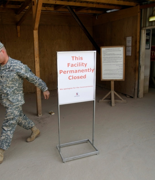 In this Oct. 15, 2011, file photo, a U.S. Army soldier walks past a sign outside a base exchange after its closure at Camp Victory Base Complex that was set to close in Baghdad, Iraq. (Khalid Mohammed/AP)