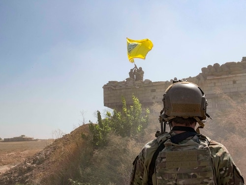 A U.S. soldier oversees members of the Syrian Democratic Forces on Sept. 21, 2019, as they demolish a Kurdish fighters' fortification and raise a Tal Abyad Military Council flag over the outpost as part of the so-called