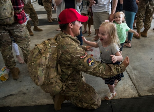 Staff Sgt. Sean Melville, a pavements craftsman with the 823rd Red Horse Squadron, reunites with his children after returning from a 183-day deployment, March 30, 2018. Under new policies, the Air Force hopes to give airmen more time at home with their families prior to deployments. (Staff Sgt. Marleah Cabano/Air Force)