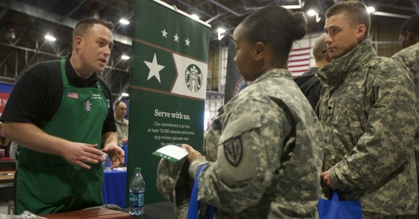 Starbucks recruiter and Air Force veteran Afsheen Saatchi, left, talks with Spc. Shaquille Armstrong, center, during the Washington State Service Member for Life Transition Summit Job Fair at Joint Base Lewis-McChord, Wash. Starbucks, which has a goal to hire 25,000 veterans and military spouses by 2025, is one of many companies across the country that have established veteran hiring initiatives in recent years. (Stephen Brashear/AP Images for U.S. Chamber of Commerce Foundation)
