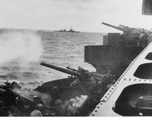 The view of the heavy cruiser Northampton's port side 5-inch/25 caliber guns in action against Japanese held Wotje Island, Maloelap Atoll, Marshall Islands, 1 February 1942. Note heavy cruiser Salt Lake City in background center. (U.S. Naval History and Heritage Command)