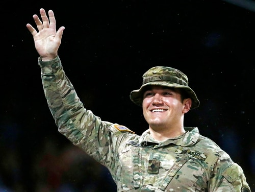 In this May 13, 2016, file photo, Oregon Army National Guard Spc. Aleksander Reed Skarlatos waves to the crowd during a tribute in the fourth inning of a baseball game between the Boston Red Sox and the Houston Astros in Boston. Roseburg, Ore., resident Skarlatos, who helped stop a gunman on a train traveling from Amsterdam to Paris in August 2015, announced his candidacy May 15, 2018, for Douglas County commissioner. (Michael Dwyer/AP)