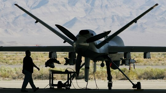 CREECH AIR FORCE BASE, NV - AUGUST 08: Michael Martinez, airframe and power plant mechanic with General Atomics Aeronautical Systems Inc., inspects an MQ-9 Reaper during a pre-flight check August 8, 2007 at Creech Air Force Base in Indian Springs, Nevada. The Reaper is the Air Force's first