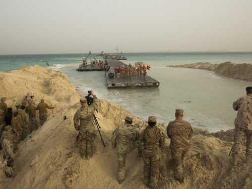 U.S. service members and United Arab Emirates Armed Forces watch the arrival of a floating causeway, Trident Pier, arrival to shore during exercise Native Fury 20 in the United Arab Emirates, March 9. (Sgt. Logan Block/Marine Corps)