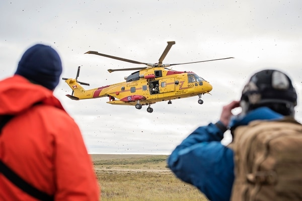 Alaska Air National Guard and Royal Canadian Air Force search and rescue personnel wait for a Canadian CH-149 Cormorant helicopter from 442 Transport and Rescue Squadron to land to extract simulated casualties during exercise Arctic Chinook, near Kotzebue, Alaska, on Aug. 24, 2016. (Staff Sgt. Edward Eagerton/U.S. Air National Guard)